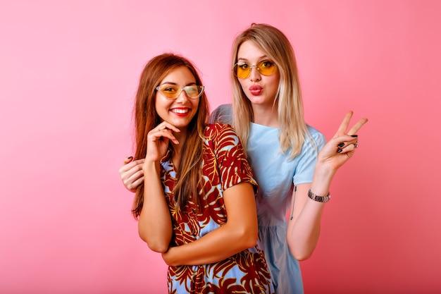 Duas irmãs bonitas felizes, melhores amigas, mulheres hipster se divertindo juntas no fundo rosa do estúdio