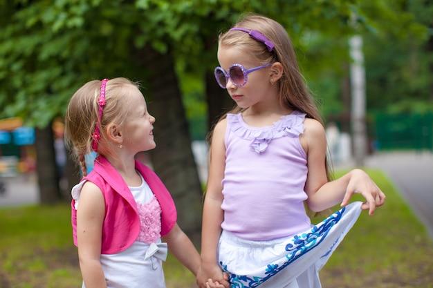 Duas irmãs bonitos de moda andam de mãos dadas no parque