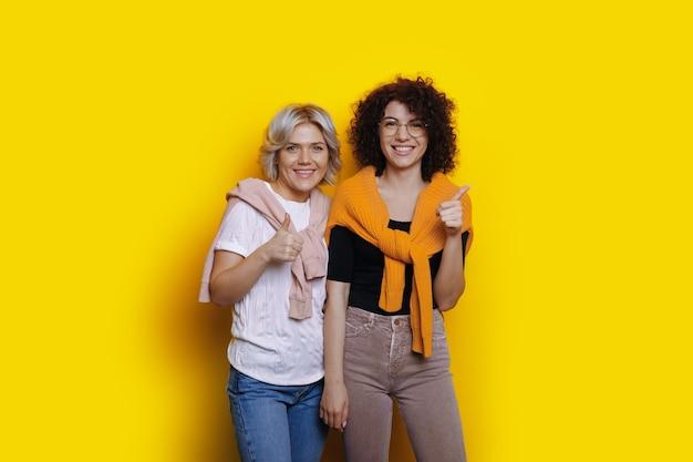 Duas irmãs brancas com cabelo encaracolado gesticulando como um sinal de semelhante enquanto torcem por um fundo amarelo