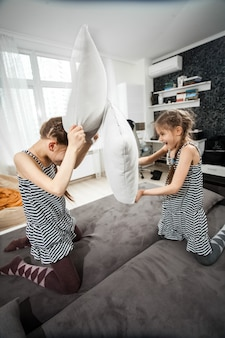 Duas irmãs brigando de travesseiro no sofá