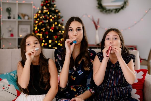 Duas irmãs brincalhonas e uma jovem mãe em casa na época do natal, sentadas no sofá na sala de estar, soprando um soprador de festa olhando para a câmera