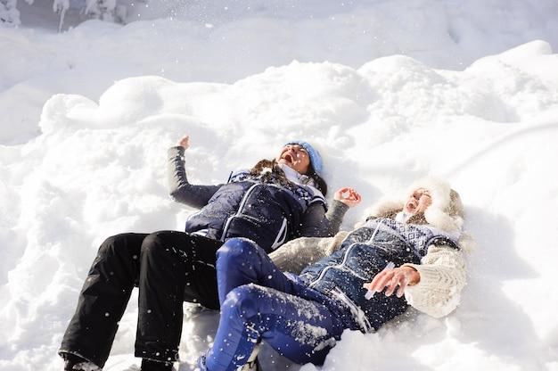 Duas irmãs brincando com neve e se divertindo no inverno, melhores amigos casal ao ar livre.