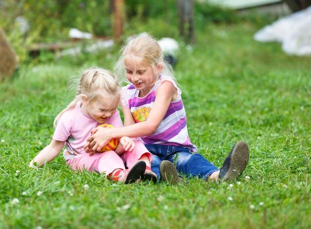 Duas irmãs brincando na campina com ball
