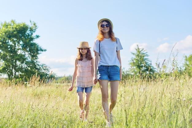 Duas irmãs caminhando juntas de mãos dadas