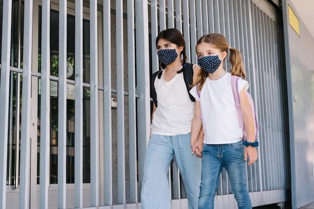 Duas irmãs caucasianos de diferentes idades entrando na escola com máscaras em seus rostos da pandemia de coronavírus covid19