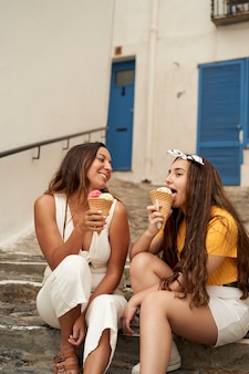 Duas irmãs com sorvete juntos ao ar livre. conceito de amizade, verão, família ...
