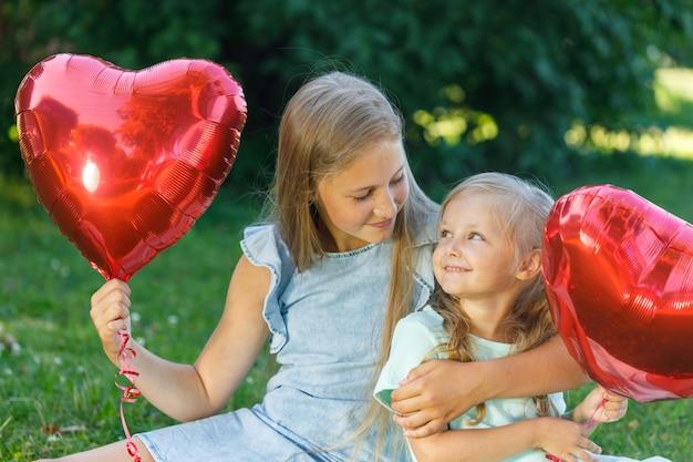 Duas irmãs com um balão em forma de coração na natureza