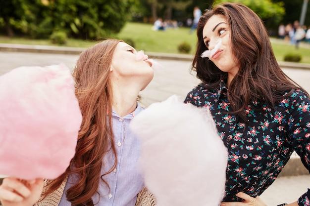 Duas irmãs comendo algodão doce no parque