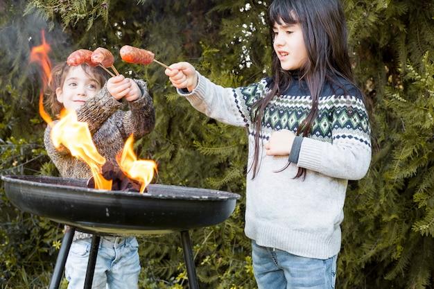 Duas irmãs cozinhar salsichas na churrasqueira portátil
