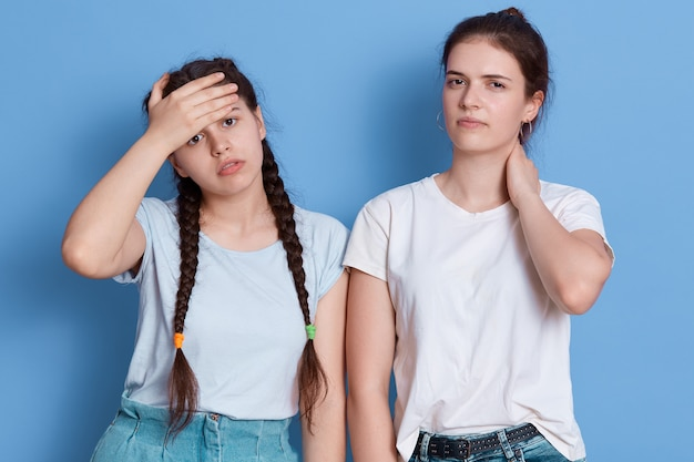 Duas irmãs de cabelos escuros posando em um ambiente fechado contra uma parede azul