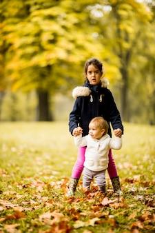 Duas irmãs de garotinha no parque outono