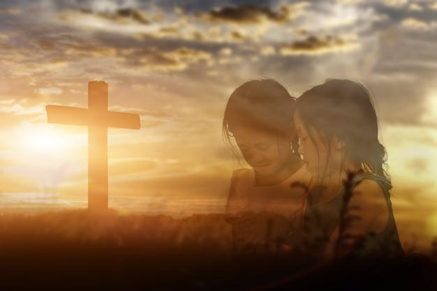Duas irmãs de mãos dadas adoram e louvam a deus ao fundo do sol. conceito de religião cristã.