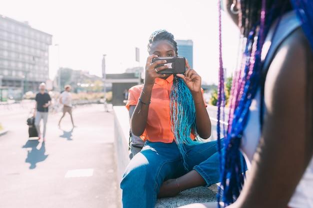 Duas irmãs de mulheres ao ar livre usando telefone inteligente tirando fotos