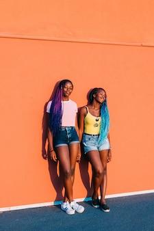 Duas irmãs de mulheres posando cidade ao ar livre a desviar o olhar