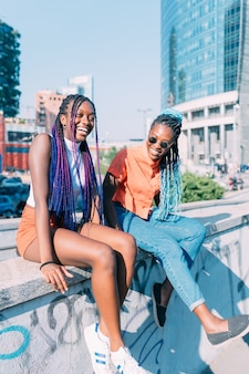 Duas irmãs de mulheres sentadas ao ar livre se divertindo juntos
