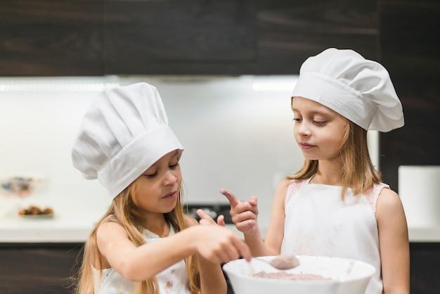 Duas irmãs, em, cozinha, desgastar, chapéu cozinheiro, olhar, messy, dedo, enquanto, levando cacau, pó