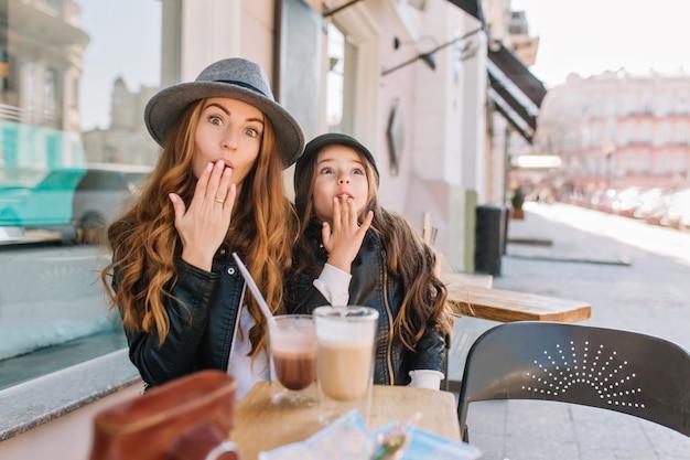 Duas irmãs encaracoladas de cabelos compridos, olhando com amor um para o outro, aproveitando a manhã ensolarada no café ao ar livre.
