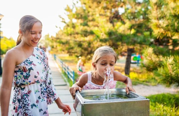 Duas irmãs engraçadas, alegres e maravilhosas bebem água fresca de uma pequena fonte em um parque ensolarado e quente de verão em férias há muito aguardadas