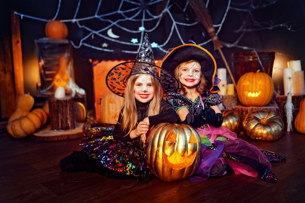 Duas irmãs engraçadas bonitos comemoram o feriado. crianças alegres em fantasias de carnaval prontas para o halloween.