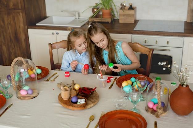 Duas irmãs estão ocupadas colorindo ovos de páscoa na cozinha