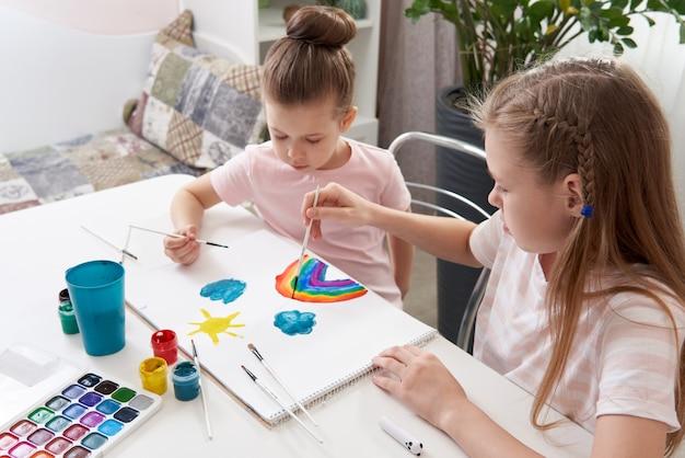 Duas irmãs felizes pintando em casa, desenho de arco-íris