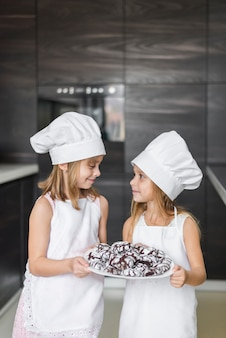 Duas irmãs fofos olhando uns aos outros segurando biscoitos assados