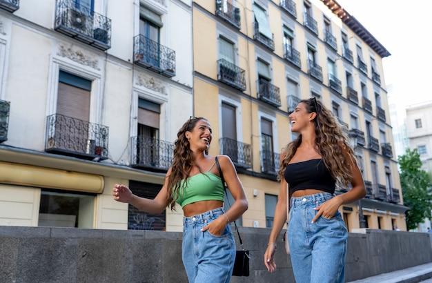 Duas irmãs gêmeas caminhando pela cidade