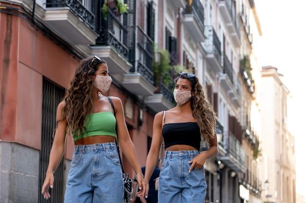 Duas irmãs gêmeas com máscaras percorrendo a cidade