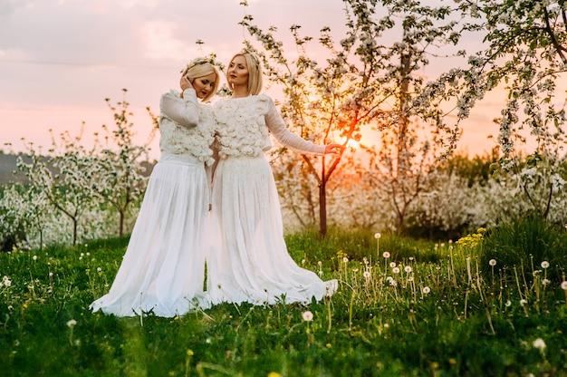 Duas irmãs gêmeas em um pomar de cereja