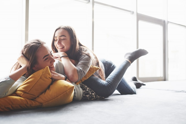 Duas irmãs gêmeas jovem bonita, passar um tempo junto com almofadas. irmãos se divertindo em casa conceito