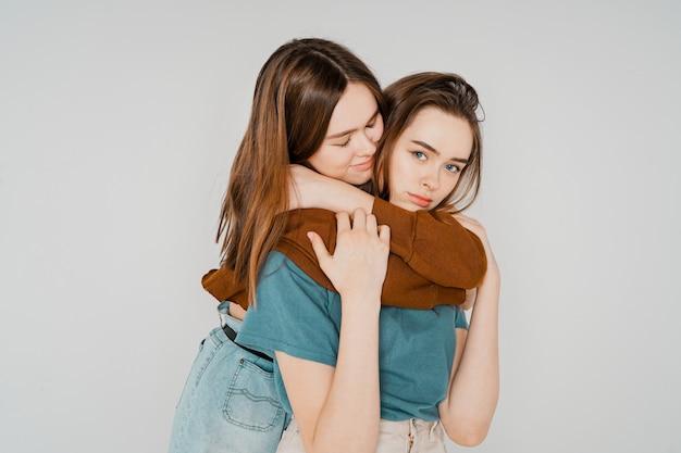 Duas irmãs gêmeas lindas meninas descolados em roupas casuais na