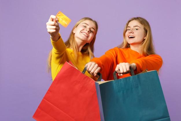 Duas irmãs gêmeas loiras engraçadas com roupas vivas, segurando o cartão do banco de crédito, sacola de pacote com compras depois de fazer compras isoladas na parede azul violeta. conceito de família de pessoas.