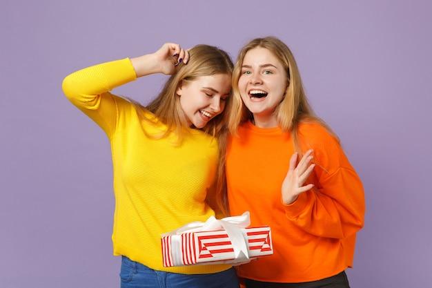 Duas irmãs gêmeas loiras surpresas com roupas vivas seguram uma caixa de presente listrada vermelha com fita de presente isolada na parede azul violeta. aniversário de família de pessoas, conceito de férias.