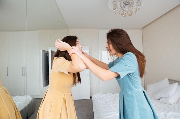 Duas irmãs gêmeas loucas e irritadas de pé e discutindo no quarto