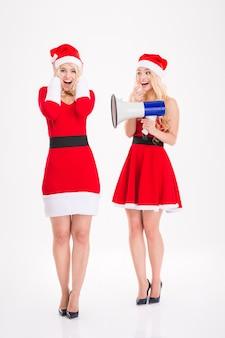 Duas irmãs gêmeas louras brincalhonas em vestidos de papai noel se divertindo com o megafone sobre fundo branco