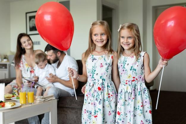 Duas irmãs gêmeas posam com balões