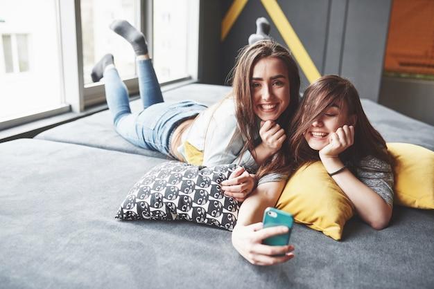 Duas irmãs gêmeas sorridentes fofos segurando o smartphone e fazendo selfie.