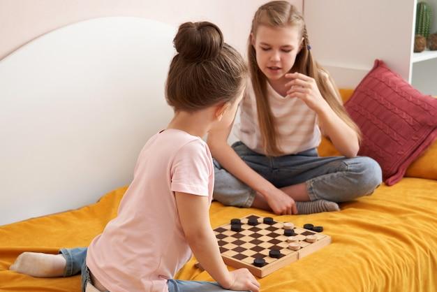 Duas irmãs jogando damas em um mau se divertindo em casa, conceito de crianças felizes