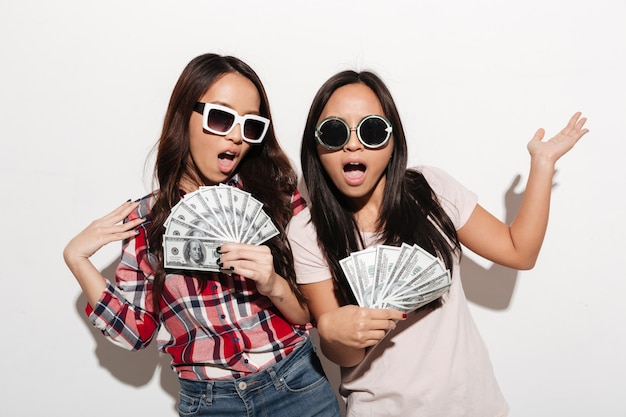 Duas irmãs legais asiáticas senhoras segurando o dinheiro.