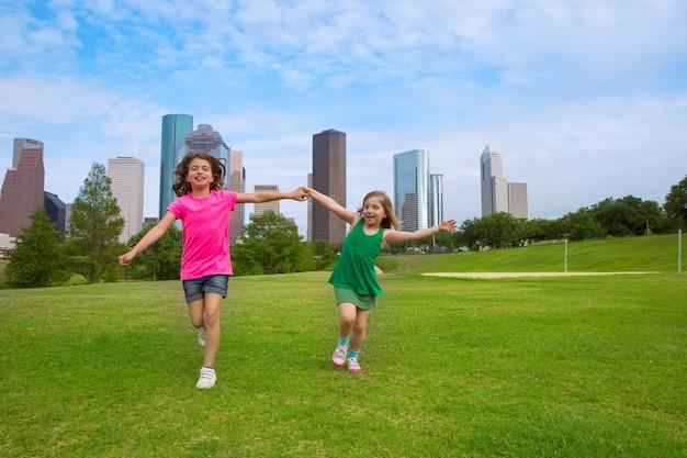 Duas irmãs meninas amigos correndo segurando a mão no horizonte urbano