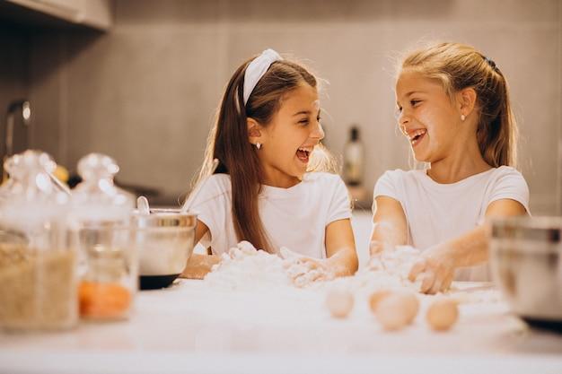 Duas irmãs meninas cozinhando na cozinha