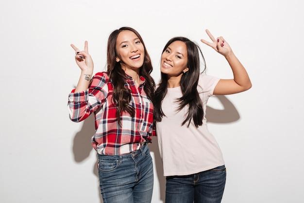 Duas irmãs muito alegres asiáticas das senhoras que mostram o gesto da paz.