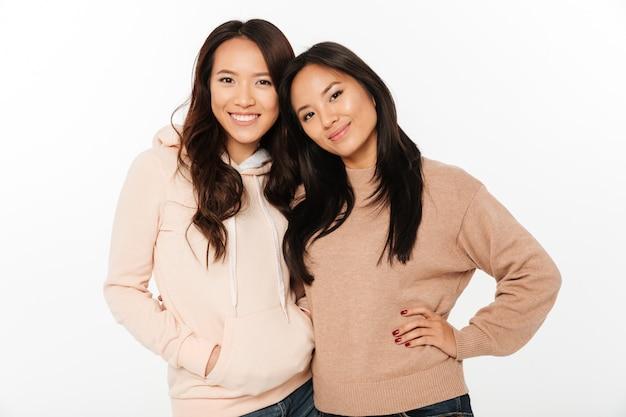 Duas irmãs muito alegres asiáticas das senhoras