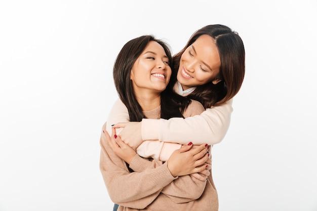 Duas irmãs muito felizes asiáticas senhoras abraçando