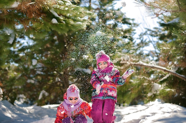 Duas irmãs no inverno em um bosque nevado brincando na neve