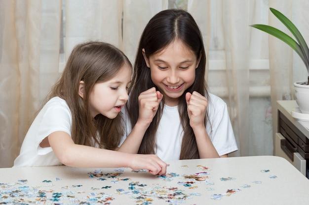 Duas irmãs pequenas engraçadas brincando juntas em uma mesa perto da janela, colecionando quebra-cabeças