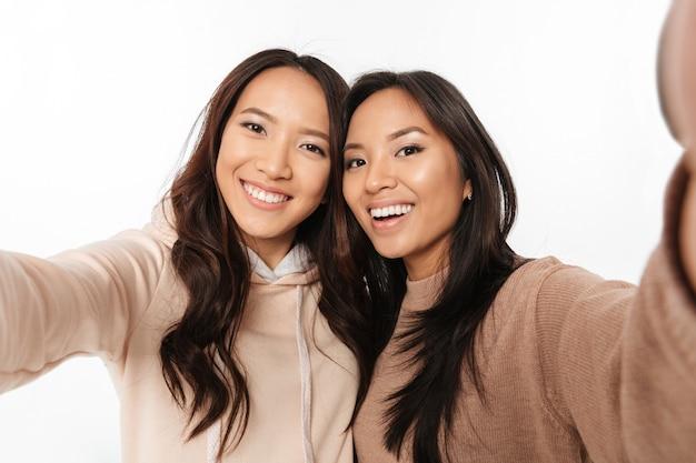 Duas irmãs positivas felizes asiáticas das senhoras