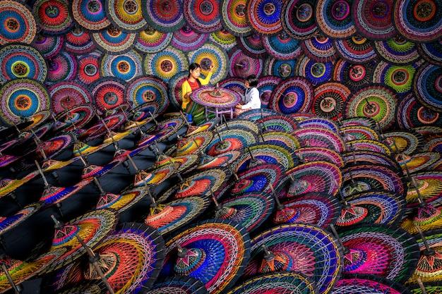 Duas irmãs que fazem guarda-chuvas birmaneses tradicionais guarda-chuvas coloridos no mercado de rua em bagan, myanmar (burma). guarda-chuvas birmaneses