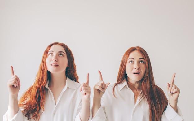 Duas irmãs ruivos estão isoladas em um fundo branco em camisas grandes e espaçosas. duas meninas apontam para cima com os dedos indicadores.