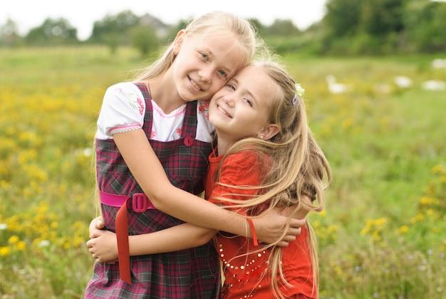 Duas irmãs se abraçam ao ar livre
